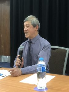 Cheng Hock Kua sitting at a table presenting his Keynote Speech