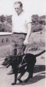 Thomas Blair walking next to black guide dog a black and white photo