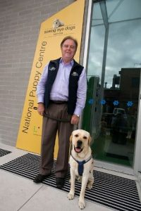 Leigh Garwood standing next to a Seeing Eye Dog and a Yellow Banner of Seeing Eye Dogs National Puppy Centre